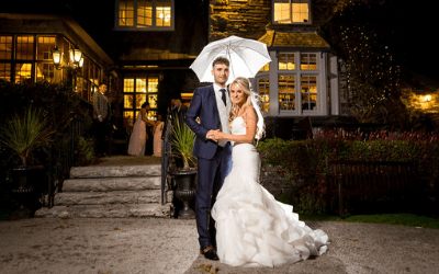 Bride & groom stand in front of Broadoaks Country House in Windermere