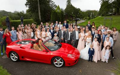 Ferrari wedding car and wedding guests at the front of Broadoaks lake district wedding venue