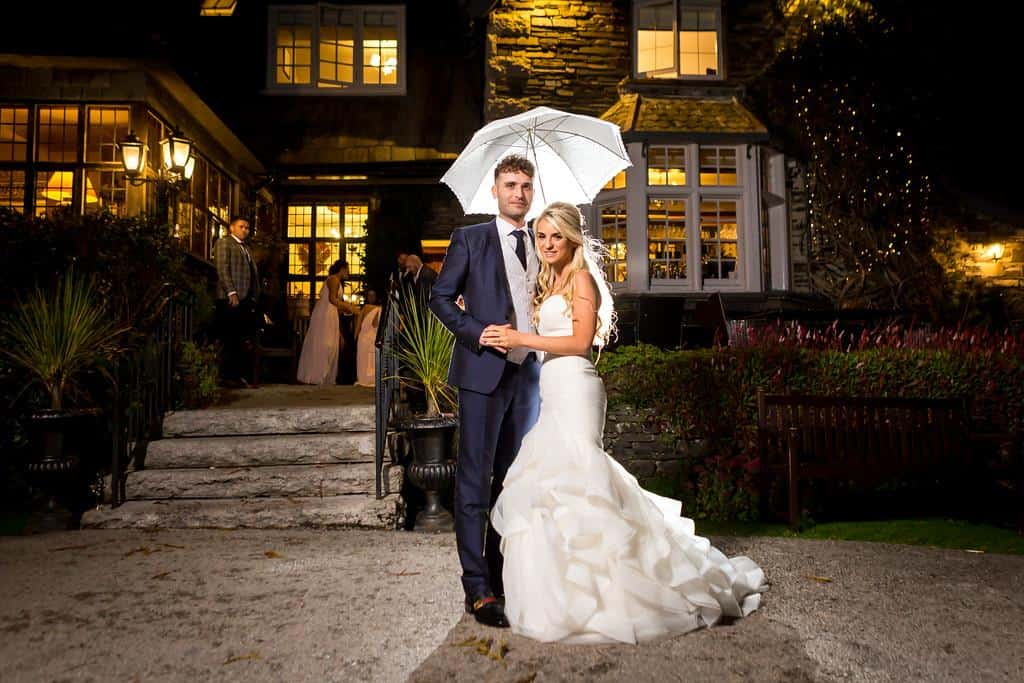 Bride & groom stand in front of Broadoaks Country House in Windermere with umbrella
