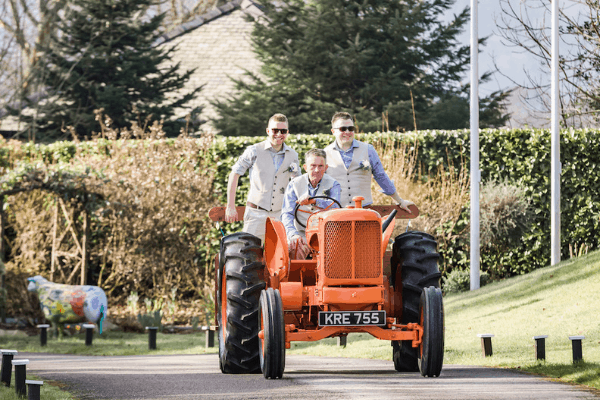 Tractor wedding vehicle arrival two grooms at Broadoaks Country Themed Wedding